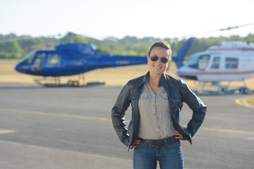 a woman next to an helicopter