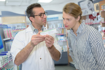 pharmacist and client looking at a product box