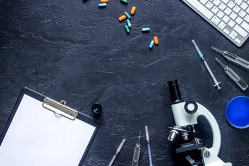Workplace of doctor. Microscope, syringe, Petri dish, pad and pills on grey stone background top view copyspace
