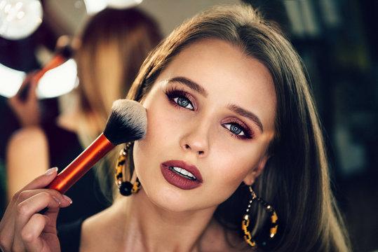 Beautiful woman doing evening makeup and holding makeup brush.