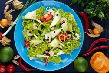 Restaurant food, healthy food, salad, freshness, restaurant menu. Top view on salad with shrimps, caviar and avocado slices on green plate, decorated with chili peppers, lime, herbs and spices