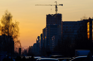 a crane over a new house construction site in the city at sunset