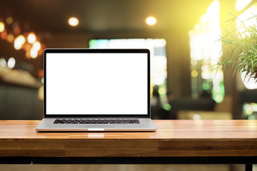 Laptop blank screen on wooden table in coffee shop morning sunshine background