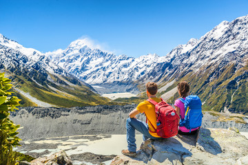 Backpackers couple hiking looking at Mount Cook view on mountains tramping in New Zealand. People hikers relaxing during hike in alps of south island.