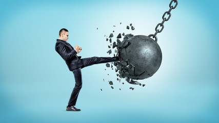 A businessman on blue background kicking at a wrecking ball and crashing it with many pieces flying away.