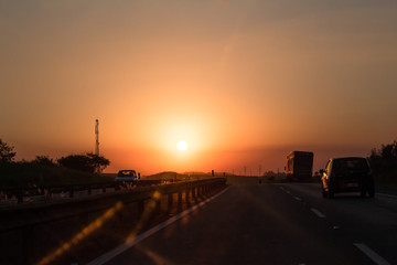 Photo of cars and truck on road at sunset