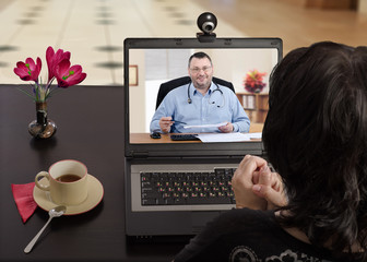 Woman nervously consults telemedicine doctor with laptop