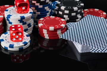 Poker chips and cards on a black background are reflected