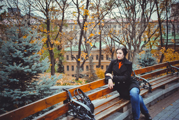 Brunette young woman plus size in black coat walk in European streets at autumn. Mystical time in town, vintage style at clothes and looks