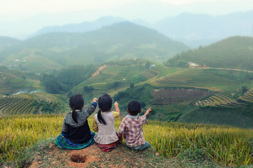 Three children looking forward on the top of terraced of rice field at Vietnam.
