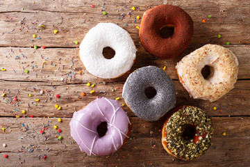 Multicolored donuts with fillings close-up on the table. horizontal top view