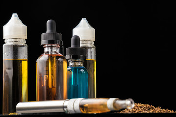 E-liquid bottles and e-cigarette with pile of grinded tobacco leaves