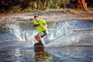 Summer sport wakeboarding. The sportsman slides on the lake's water on the board. Wall mural