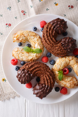 Festive almond and chocolate cookies in the shape of a horseshoe close-up. vertical top view