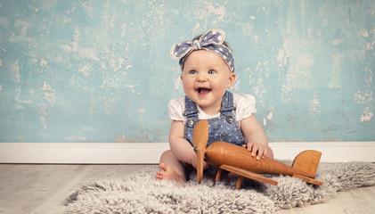 lachendes kleines Mädchen spielt mit Flieger