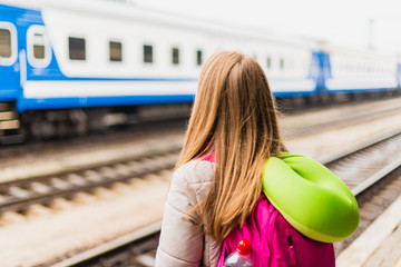 Girl is waiting for the train. Girl with a backpack and with green neck pillow