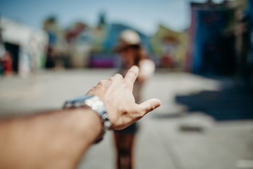 Man hand reaching woman in the street.