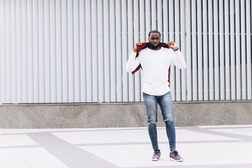 Handsome Afro American man wearing casual clothes jumping and dancing with grunge concrete wall background