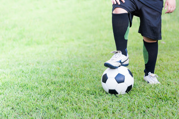 soccer ball with child feet player on green grass