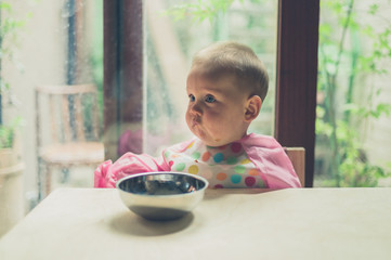 Little baby learning how to eat at table