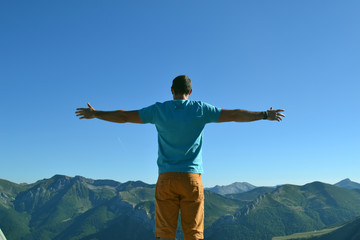 Silhouette man with hands rise up on beautiful view, upon the top of mountain. Concept freedom of life.