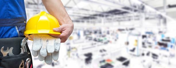 Beruf Industriearbeiter mit Ausrüstung in einer Fabrikhalle