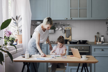 Cute little Caucasian girl and her mother drawing with crayons on kitchen table and having fun.