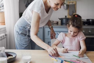 Cute little Caucasian girl and her mother drawing with crayons on kitchen table.