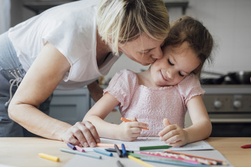 Mother and daughter drawing together with crayons on kitchen table