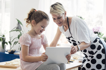 Mother and her little cute daughter using tablet at kitchen at home and smiling.