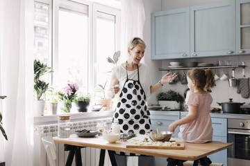 Mother and her little cute daughter playing smiling and having fun at kitchen at home.