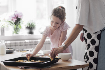 Cute little Caucasian girl enjoying arranging baked cookies with her mother at kitchen.