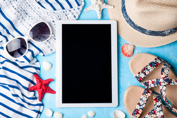 Summer women's accessories: sunglasses, hat, sandals, shirt and tablet on blue background. Vacations, travel and freelance work concept. Top view