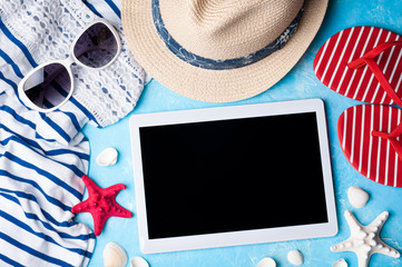 Summer women's accessories: sunglasses, hat, flip flop, shirt and tablet on blue background. Beach, vacations, travel and freelance work concept