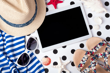 Summer women's accessories: sunglasses, hat, sandals, shirt and tablet on creative background. Vacations, travel and freelance work concept