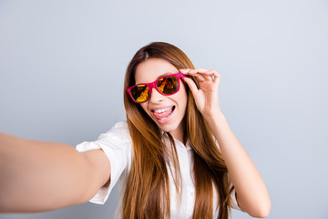 Selfie mania! Funky mood. Attractive young lady is making a selfie on the camera, flirty and playful. In pink trendy sunglasses, with tongue out, on pure light grey background
