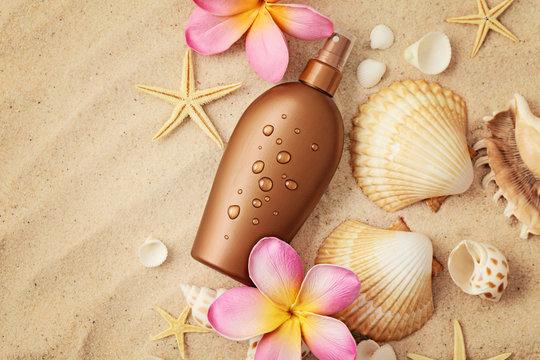 suntan lotion and seashells on sand beach