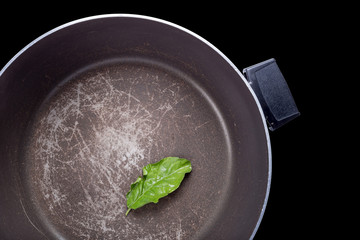 grunge frying pan with a green leaf isolated on black background