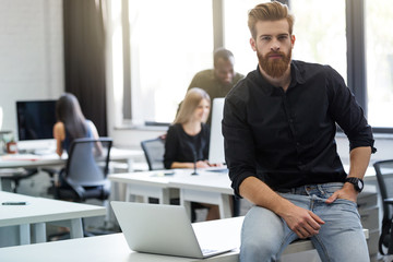 Young bearded man sitting on his desk in an office