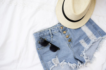 Summer clothes on white background. Sunglasses, shorts and hat