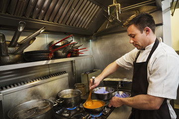 Chef standing in kitchen, wearing apron, cooking soup on a stove, stirring with ladle.