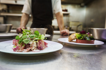 Close up of two plates of food in a kitchen, chef wearing apron standing in background.