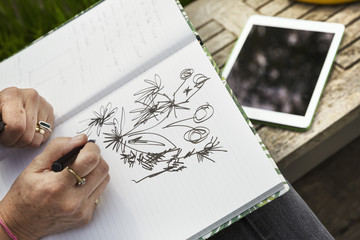 A woman sitting on a bench, drawing flowers in a sketchbook or digital tablet.