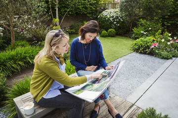 Two women sitting on a bench in a garden, looking at a portfolio with gardening images, discussing garden design.