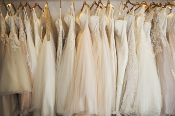 Rows of wedding dresses on display in a specialist wedding dress shop. A variety of colour tones and styles, fashionable lace and boned bodices.