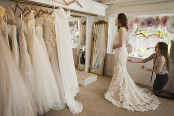 Rows of wedding dresses on display. A young woman in a full length white wedding dress, looking at her reflection in the mirror in a bridal boutique.