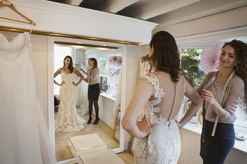 A young woman in a full length white wedding dress, looking at her reflection in the mirror in a bridal boutique. A dressmaker in the background.