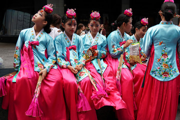 Youths in traditional Korean outfits eat Korean snack food in Times Square in the Manhattan borough of New York City