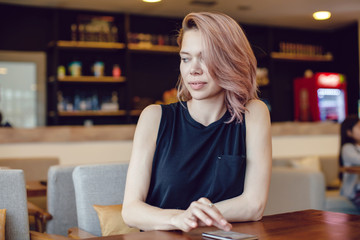 Attractive woman sitting at the cafe and using smartphone.