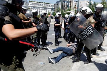 A municipal worker lies down among riot police officers at the main entrance of the parliament building during a rally against job layoffs affecting their sector in Athens
